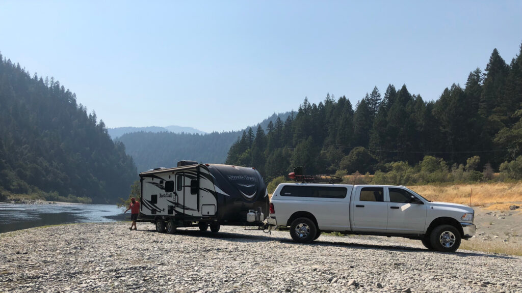 A truck and RV trailer are boondocking on a river's edge where they don't have to worry about other campers.