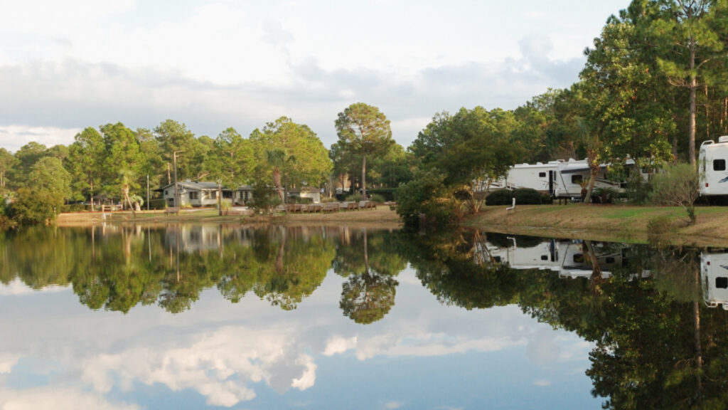 A COE campground with trees and RVs along a lake.