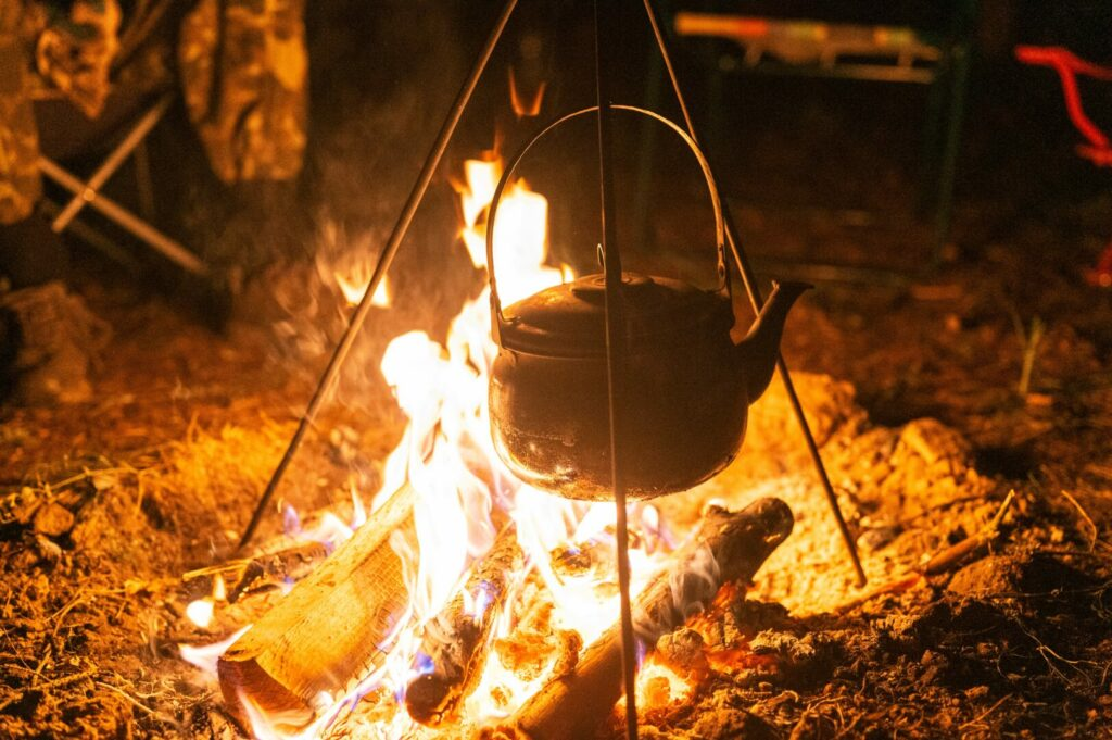 A camping kettle is hanging above a campfire to heat up.