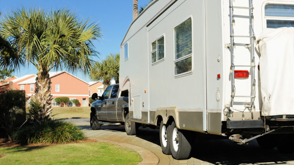 A truck brings an RV onto the driveway entering a porthome community.