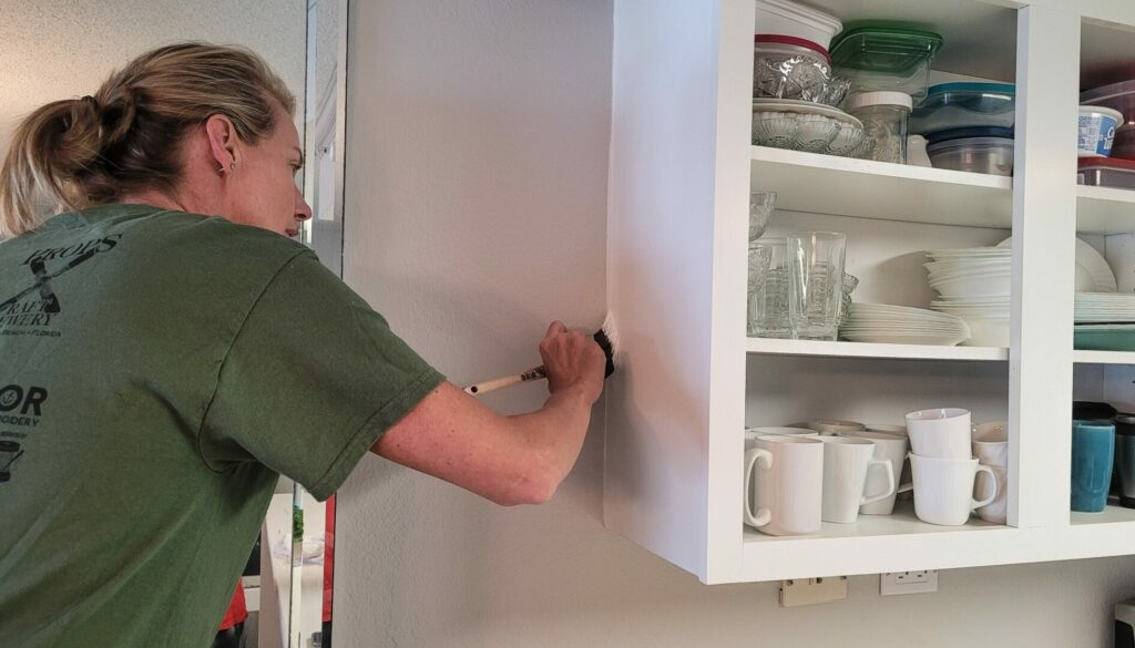 A woman uses a brush to paint corners of the cabinets.