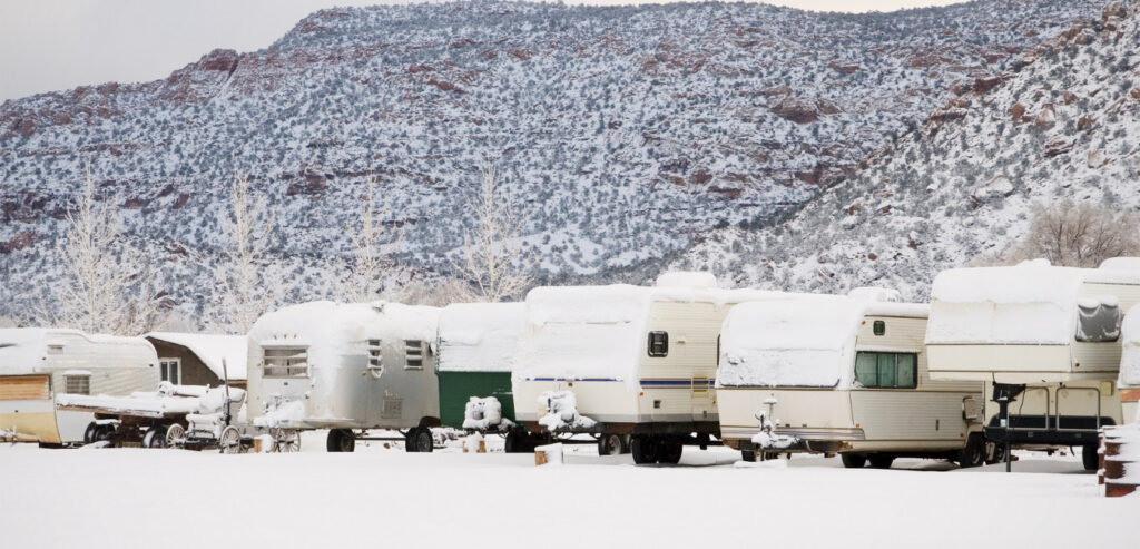RVs in a row all covered in snow while winter camping