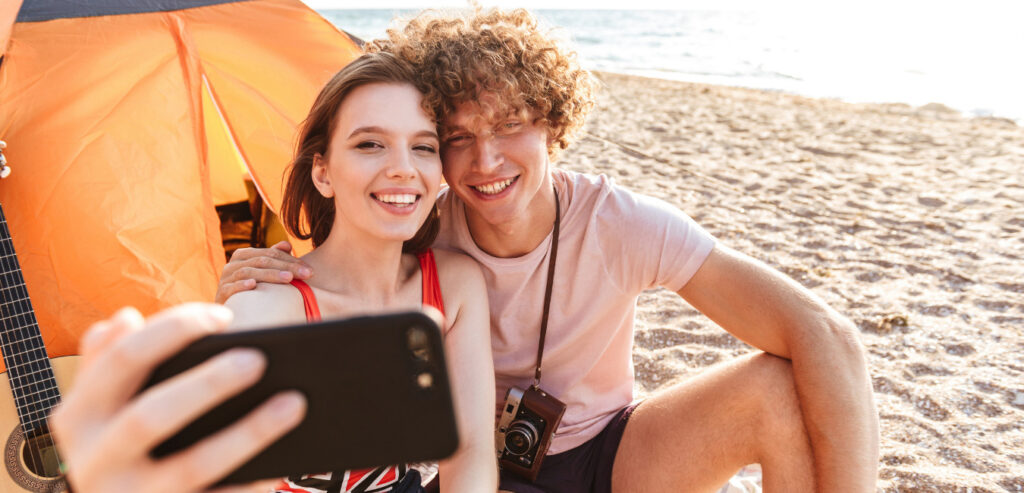 Young couple camping in Florida taking a selfie on the beach.