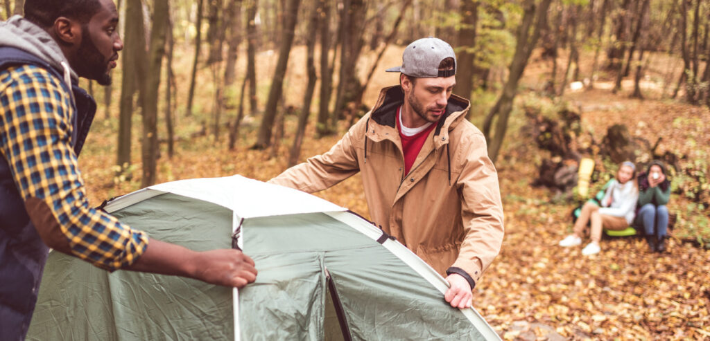 Two men pitching a tent for campers.