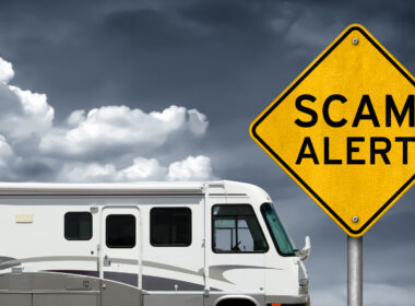 A used motorhome RV set against a dark cloudy sky with a scam alert sign.