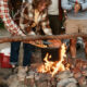 A group of friends cook a pot of food over an open campfire.