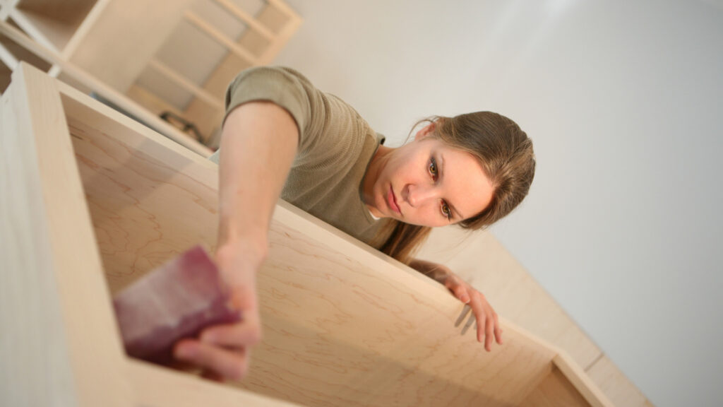 A woman sands down some wood cabinets with focus.