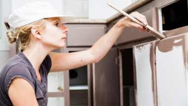 A woman paints a cabinet brown with a paintbrush.