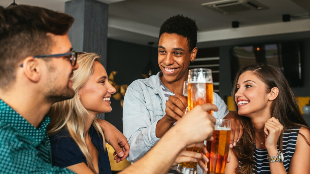 A group of friends enjoy a cheers and some beers.