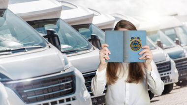 A woman holds up a Kelley Blue book while looking for RVs to buy.