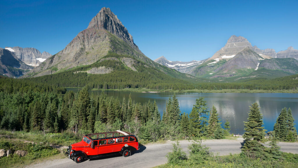 A Red Bus drives along the Going to the Sun road and takes in the beautiful alpine lake and mountain views.
