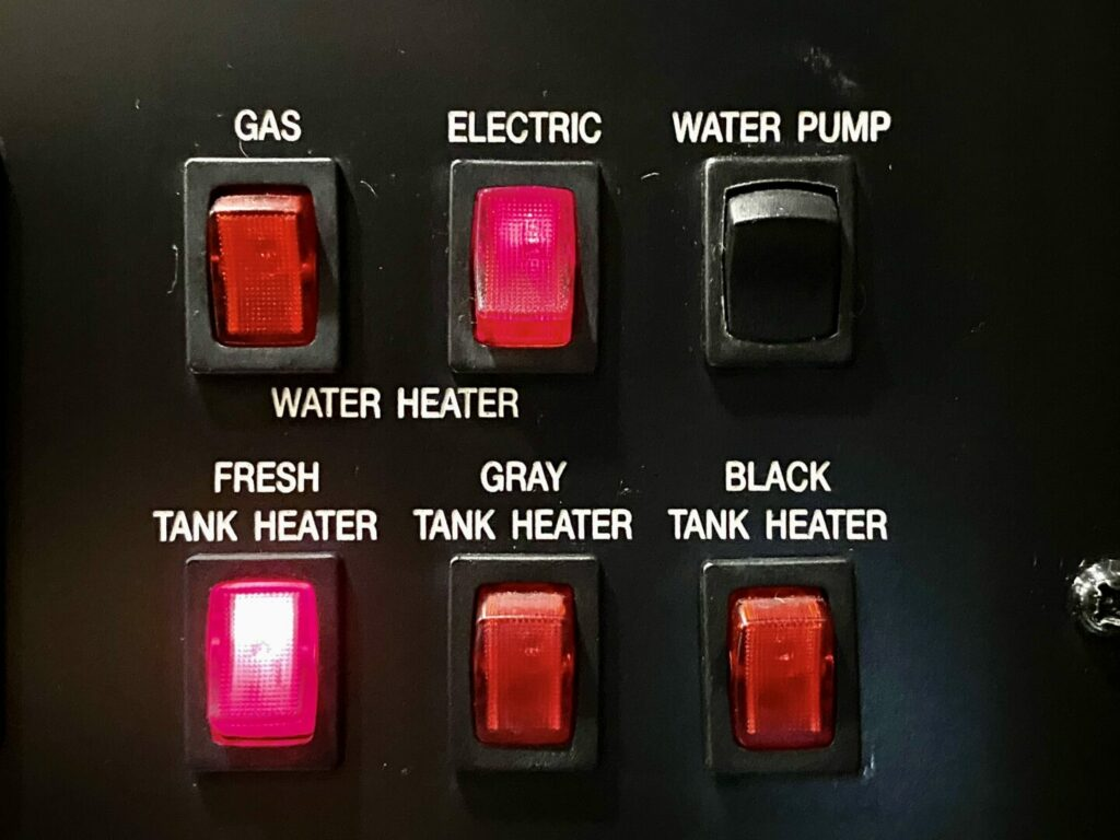RV control panel showing that the fresh water tank heater is turned on while winter camping