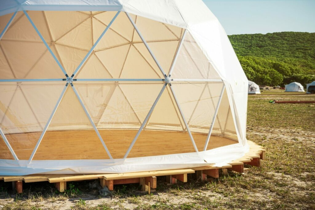Close up of a transparent camping pod on camp ground.