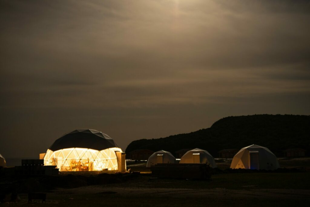 Night time image of camping pods lit up.