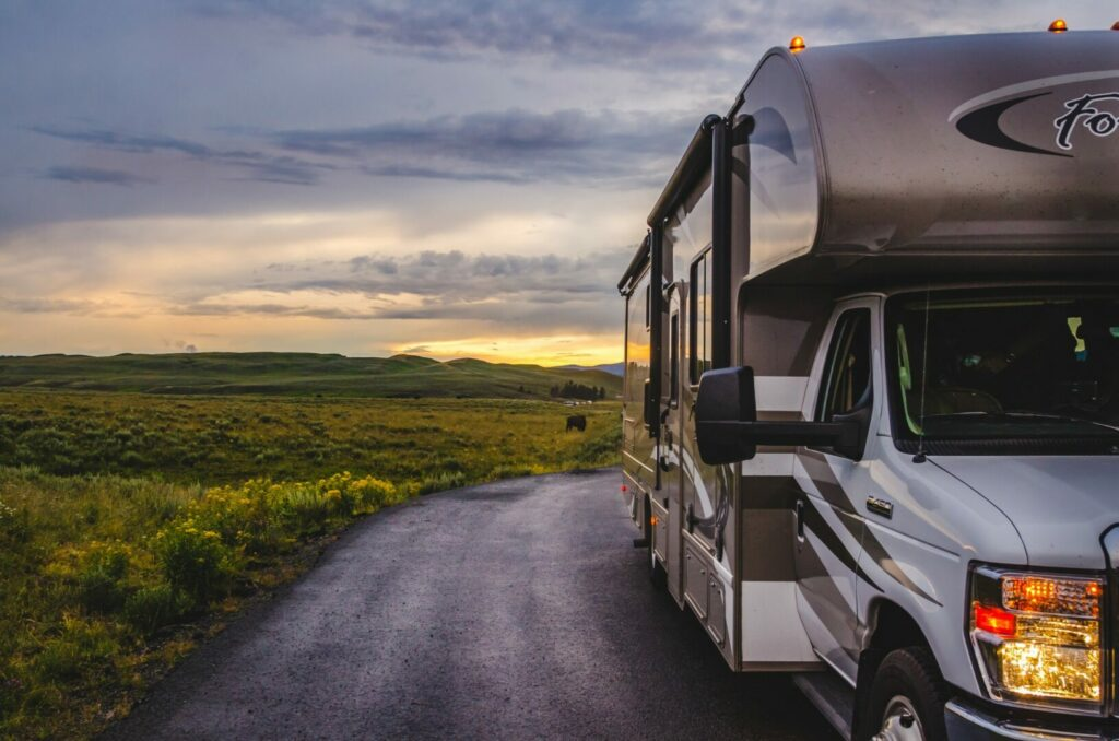 RV driving down farm road at sunset to Harvest Host site.
