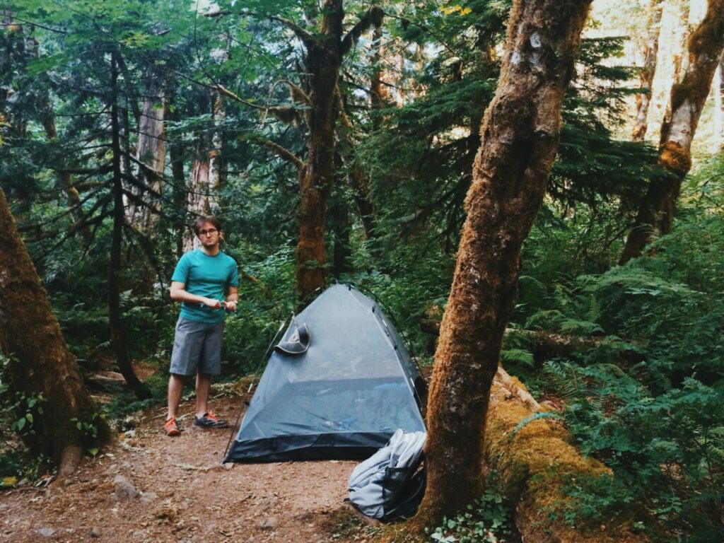 Man setting up tent in national forest to camp in oregon