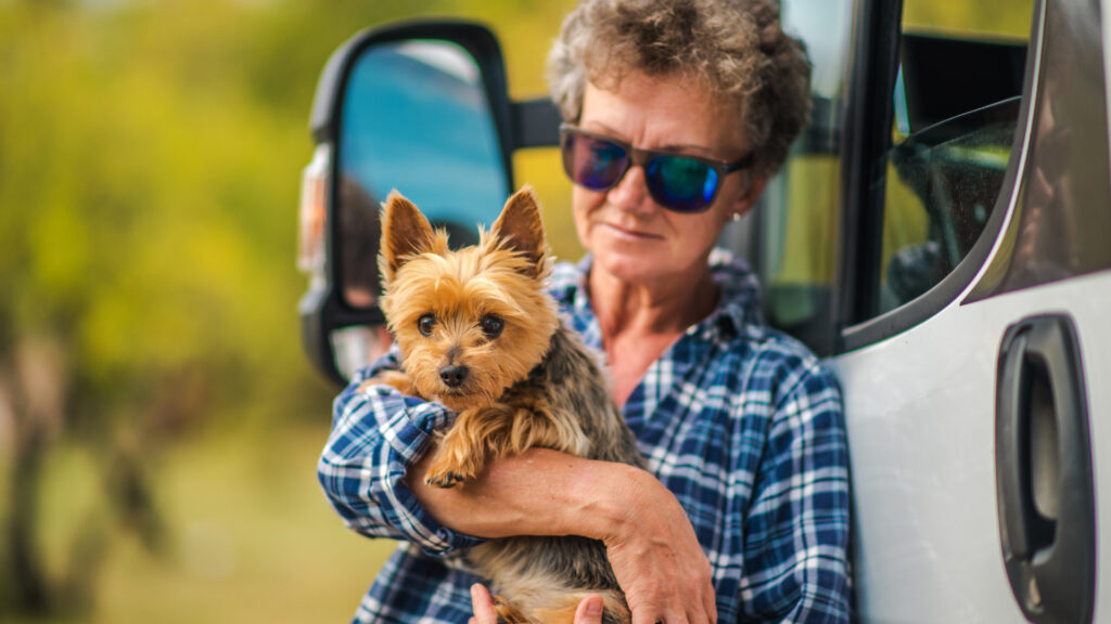 A woman holding her small dog while standing outside of her RV