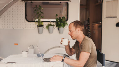 A man works on his computer while camping in his RV.