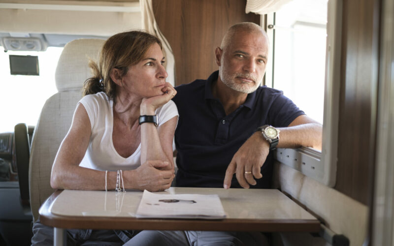 A married couple sitting in an RV looking disappointed