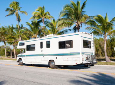An RV is driving down a palm tree lined street in Florida.