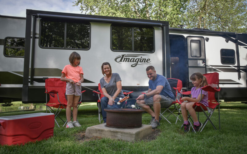 A family enjoys a campfire in front of their Grand Design Imagine travel trailer.