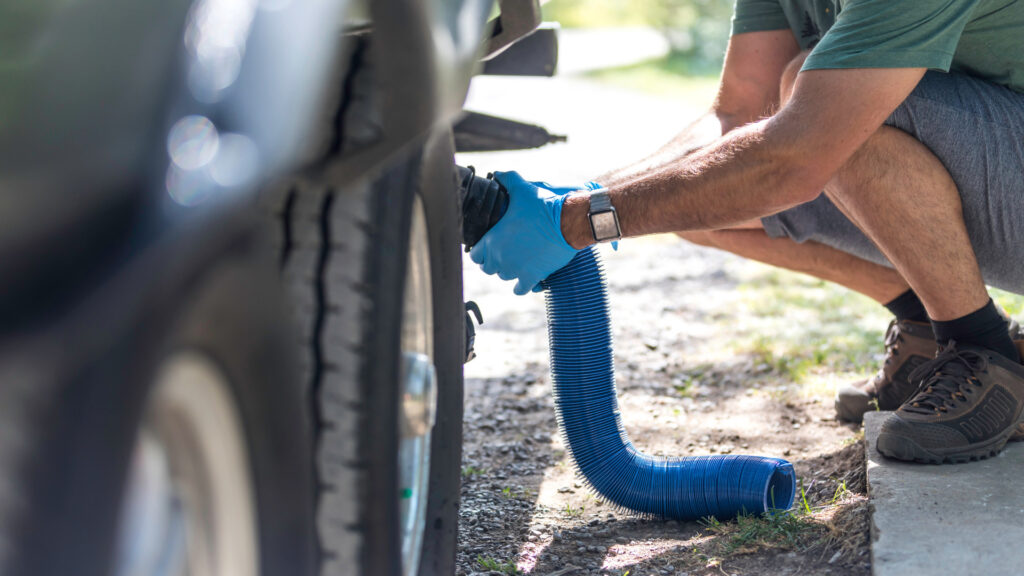 A man crouched down connecting his sewer hose to his RV