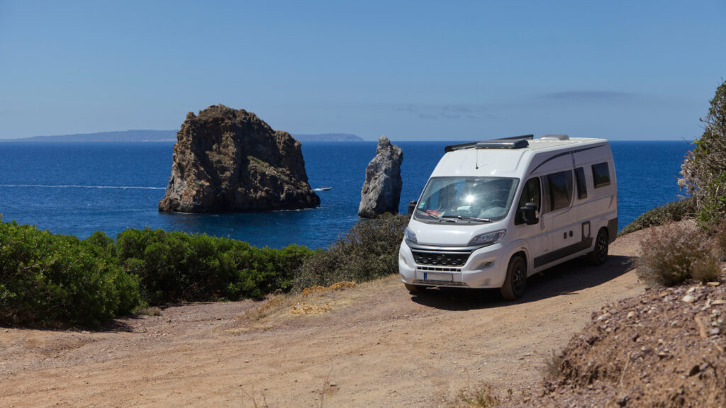 A camper van found a free camping site near the ocean and some scenic rocks.