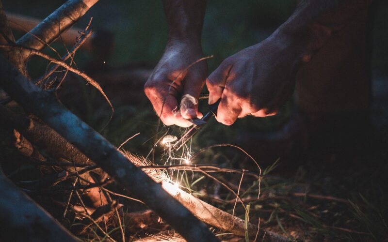 a man using a campfire starter over some loose leaves and wood