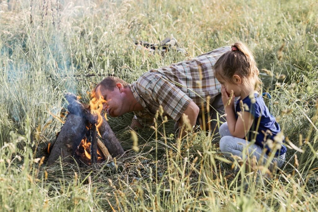 Man blowing on a campfire that he got going with a campfire starter, blowing on a fire. Little girl sitting in a grass beside a campfire.