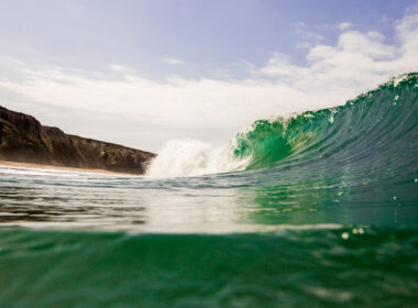 Jalama beach camping is a great surf spot with green ocean waves crashing on the shore.