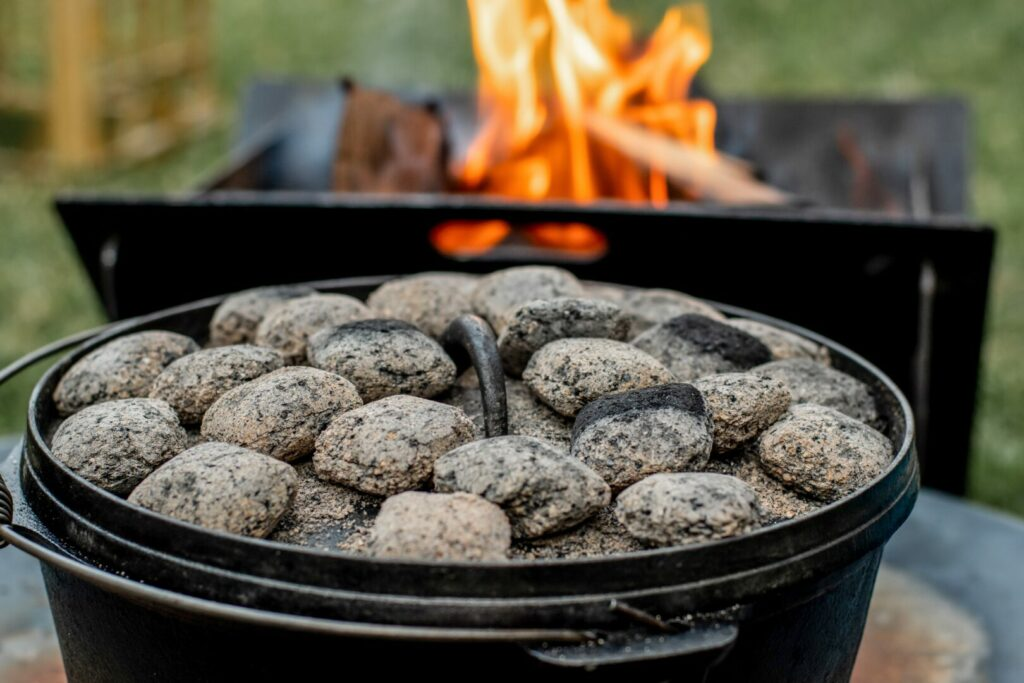 A dutch oven with coals on the lid and a campfire in the background. This is a great method for slow campfire cooking.