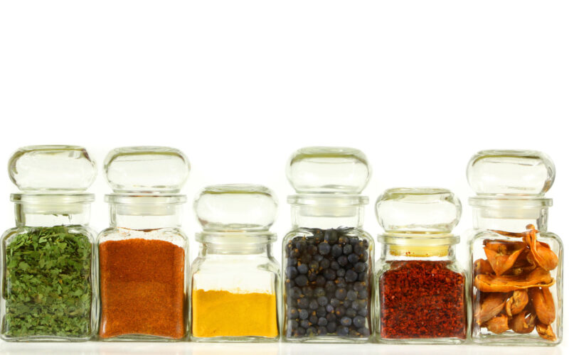 Spices lined up together in jars against a white backdrop.