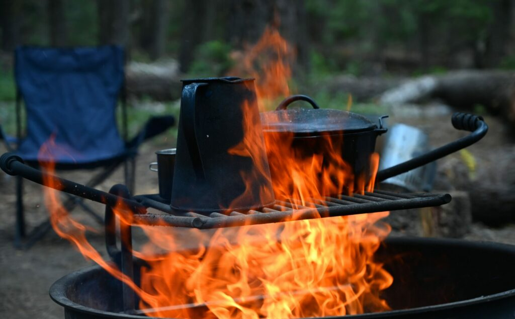 A large fire engulfing a cast iron dutch oven, a mug, and a percolator. This fire is too high for campfire cooking.