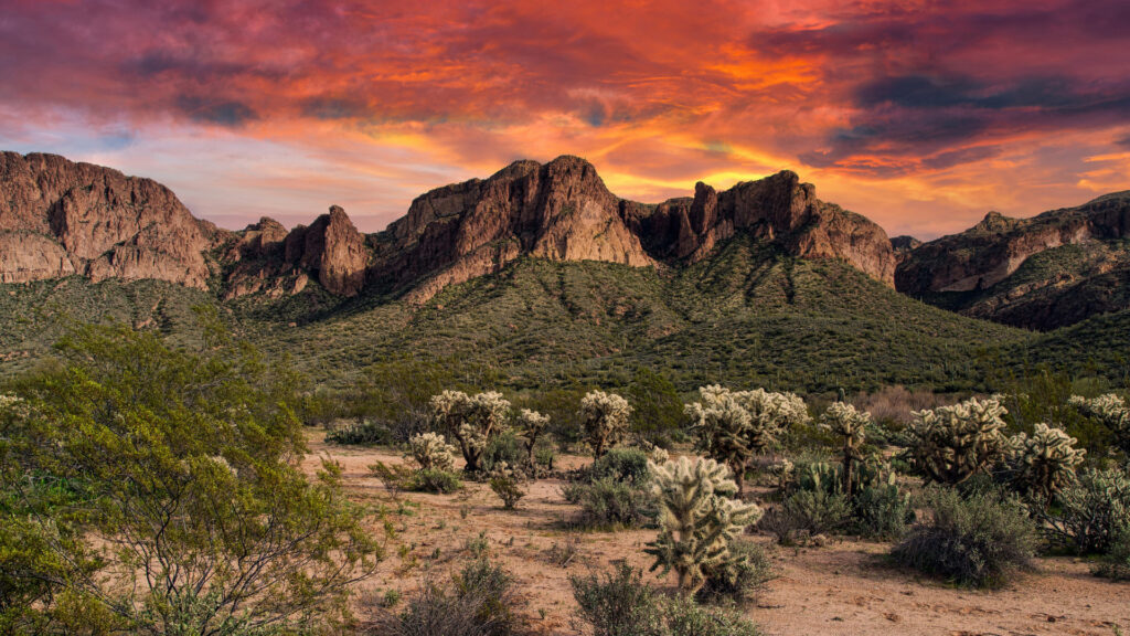 A red and orange sunset over the desert mountains and land of Tonto National Forest.