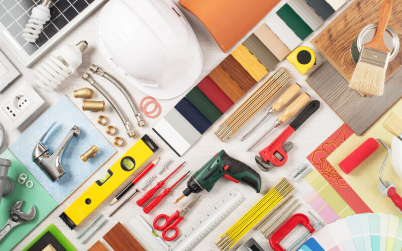 A variety of colorful RV renovation tools and paint swatches laid out.