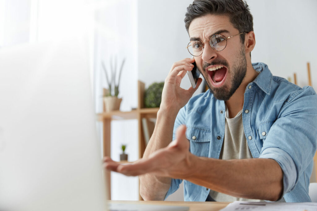 Man angry at something he is reading on his laptop computer