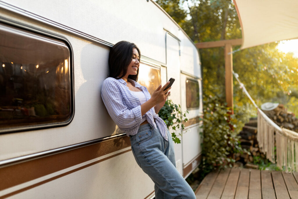 Woman using Facebook next to her RV.