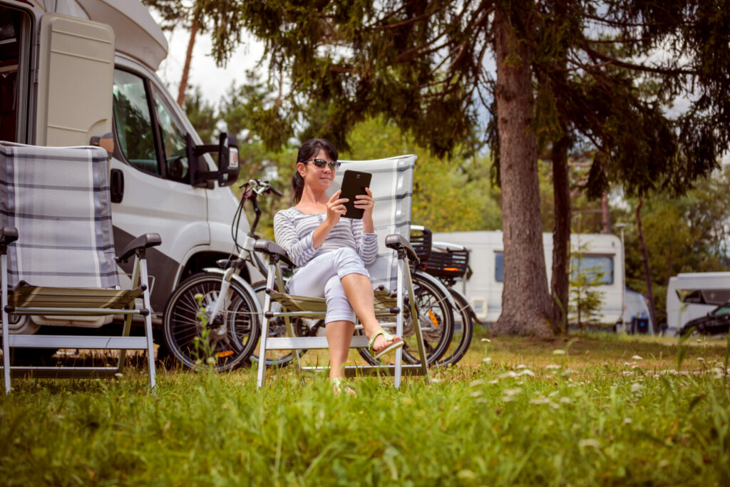Woman on tablet using facebook while at RV campsite.