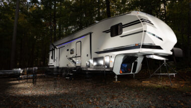 A fifth wheel toy hauler lit up in a dark camping spot.