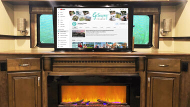 An RV living room with a fire burning and a TV playing.