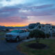 A white dodge truck and Solitude RV sit parked in a campground with a beautiful sunset in the background.