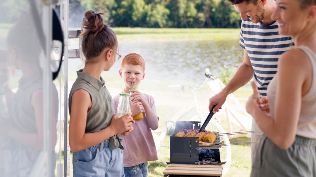 Parents grill and kids drink juice out of glass jars next to their RV near a river.
