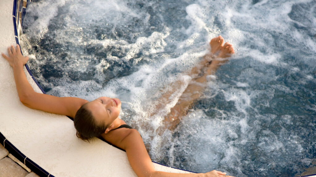 A woman soaks in a hot tub and relaxes.