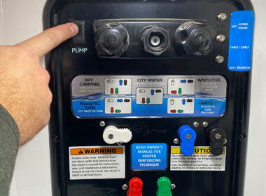 Hand pushes switch to turn off RV water pump