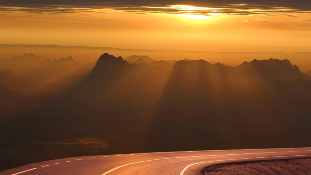 Sunset yellow rays flow over mountain tops and make an empty highway glow golden.