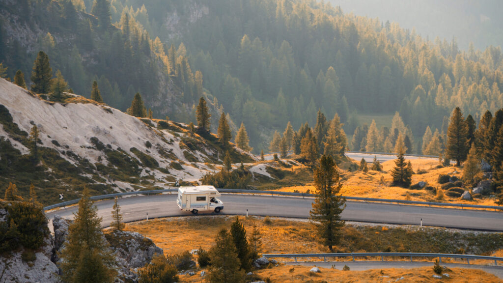 A solo RV travels across an empty windy forest road.