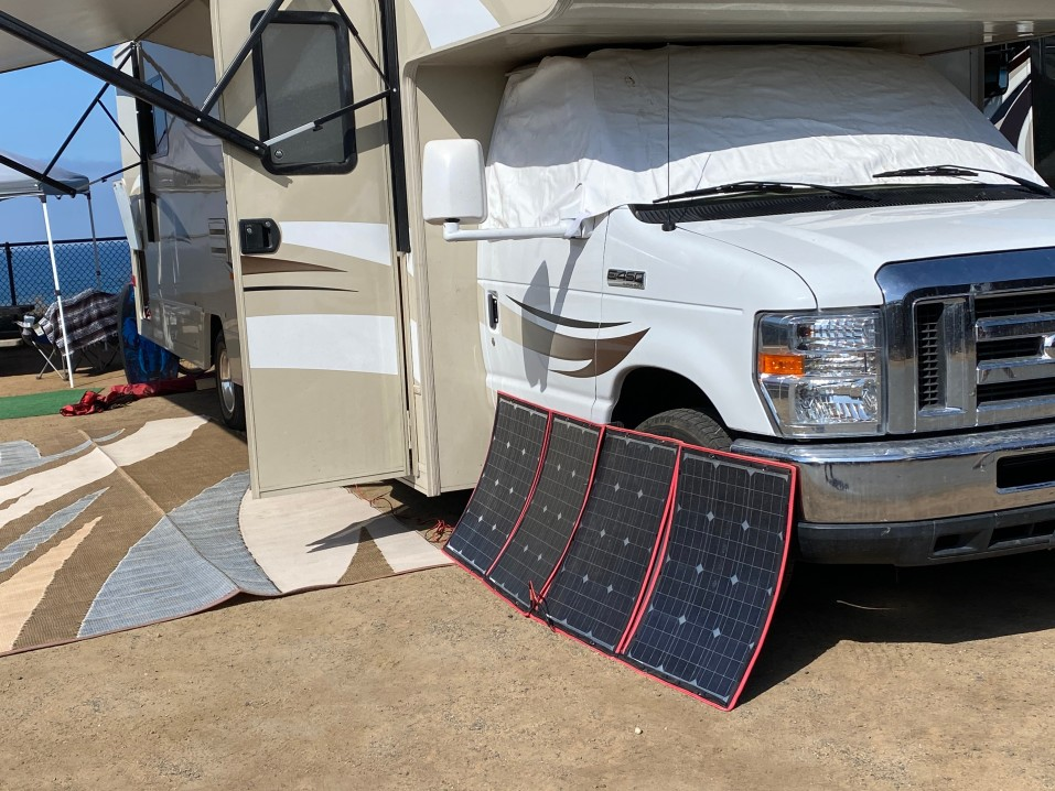 Flexible portable solar panels leaning against a motorhome in the sunshine.