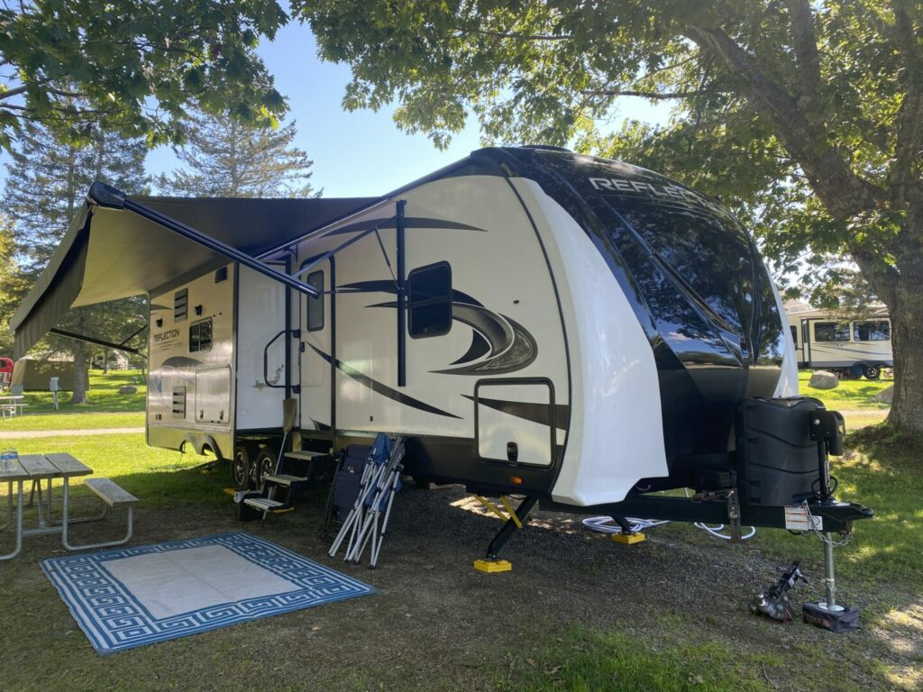 A Grand Design Reflection with it's awning out and setup at a campground