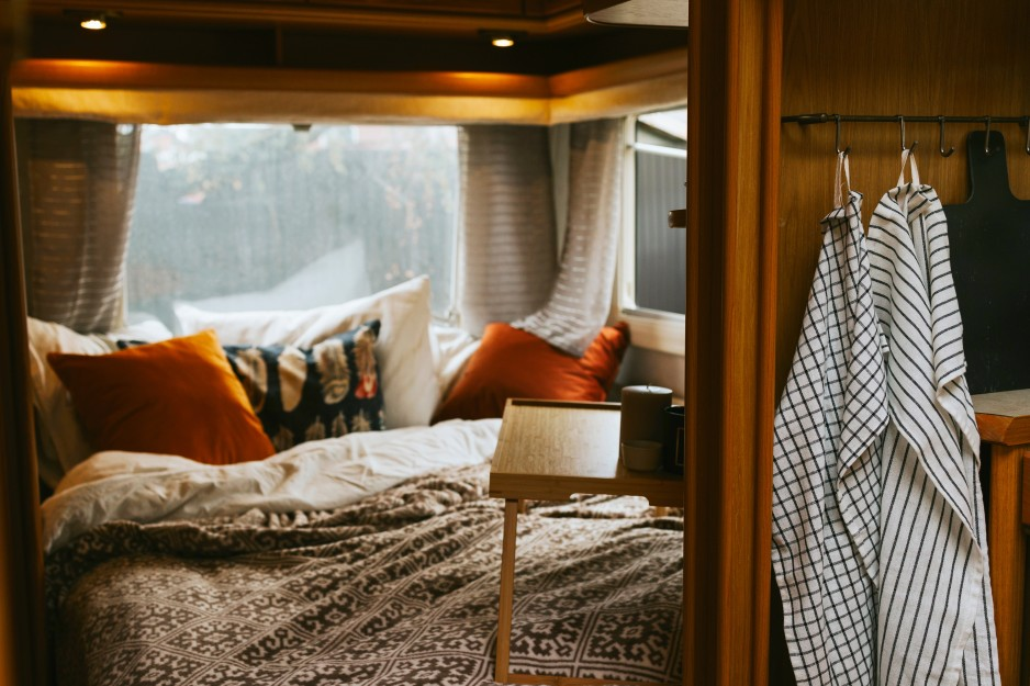 Cozy interior of four-season campers with blankets and pillows with windows looking out to forest.