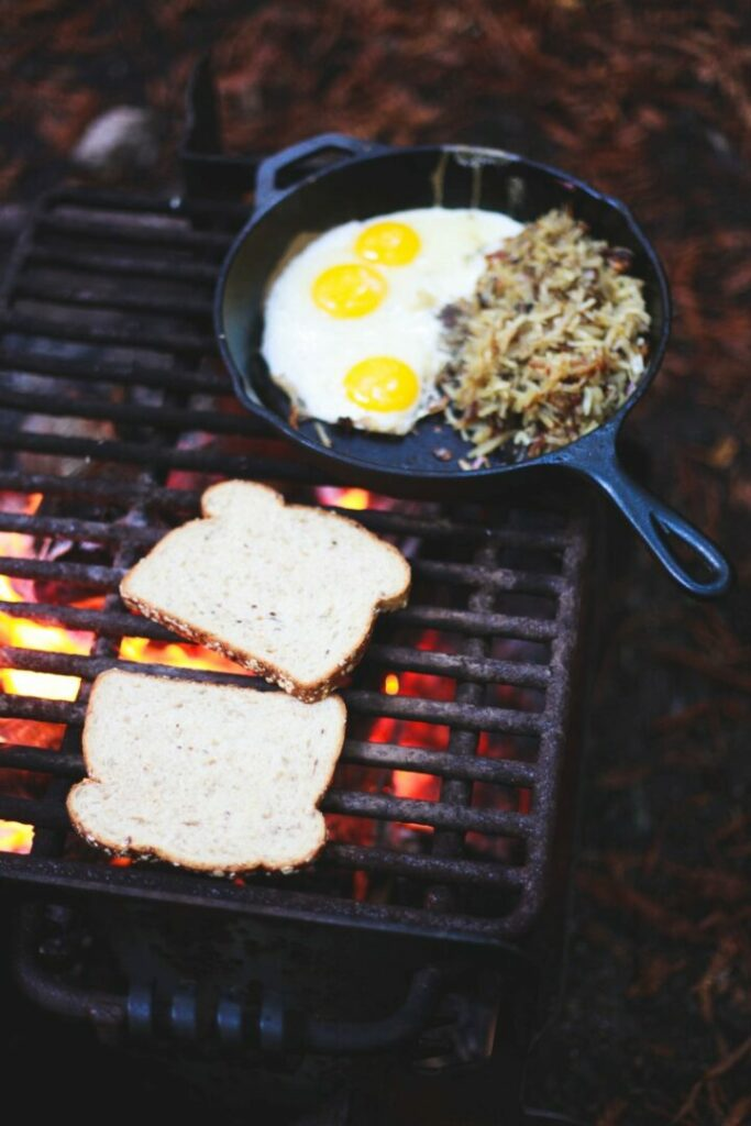 A breakfast of toast, eggs, and hashbrowns cooking on a campfire grill grate outside.